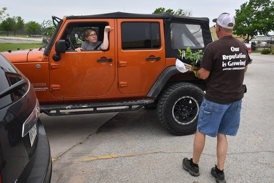 Jinna Barrett asks for her plants to be loaded in the back of her vehicle as David Chester makes a curbside delivery at Smith's Gardentown Monday morning.