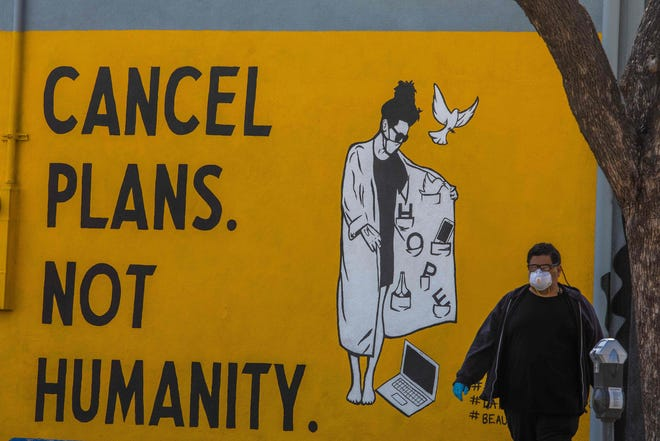 "A man wearing gloves and a face mask walks by a mural reading ""Cancel Plans Not Humanity"" during the coronavirus (COVID-19) pandemic on April 4, 2020 in Los Angeles."