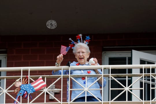 "A resident of the Lambeth House, where a cluster of COVID-19 has formed, reacts from her balcony as opera singers Irini Hymel and Bryan Hymel sing to the quarantined residents in New Orleans on March 20, 2020. As coronavirus cases spike ever higher in Louisiana, the state's nursing homes, assisted living sites and adult residential care facilities are showing more and more ""clusters"" of the virus, but the full scale of the outbreak at those sites remains uncertain."