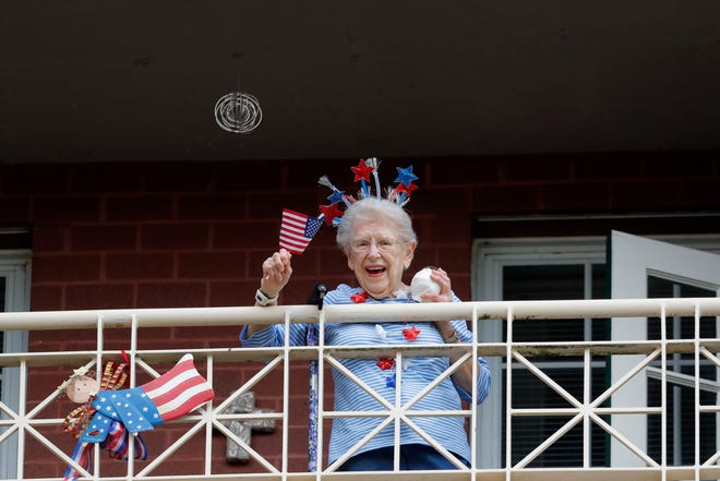 """A resident of the Lambeth House, where a cluster of COVID-19 has formed, reacts from her balcony as opera singers Irini Hymel and Bryan Hymel sing to the quarantined residents in New Orleans on March 20, 2020. As coronavirus cases spike ever higher in Louisiana, the state's nursing homes, assisted living sites and adult residential care facilities are showing more and more """"clusters"""" of the virus, but the full scale of the outbreak at those sites remains uncertain."""