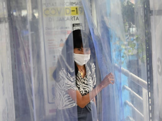 An Indonesian woman walks through a disinfection chamber as a preventive measure amid the COVID-19 coronavirus pandemic at the Harmony bus station in Jakarta on April 6, 2020.
