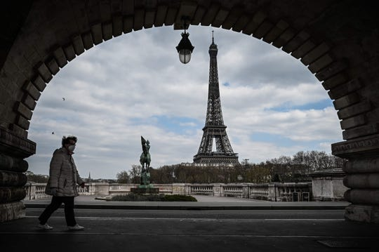 A lady carrying a protecting screen walks on the Bir-Hakeim bridge in entrance of the Eiffel Tower in Paris on April 2, 2020.