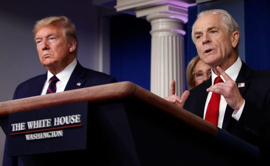 White House trade adviser Peter Navarro, who will now serve as national defense production act policy coordinator, speaks about the coronavirus in the James Brady Press Briefing Room, Friday, March 27, 2020, in Washington, as President Donald Trump listens. (AP Photo/Alex Brandon)