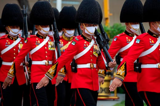 An honor guard wearing protective masks due to the spread of the COVID-19 coronavirus prepare for the arrival of Thailand's King Maha Vajiralongkorn and Queen Suthida at the King Rama I monument to mark Chakri Memorial Day that honors the founding of the ruling Chakri Dynasty in Bangkok on April 6, 2020.