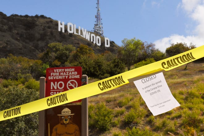 A sign is seen at the entrance to Innsdale Trail near the Hollywood Sign, Saturday, March 28, 2020, in Los Angeles near the start of the coronavirus pandemic.