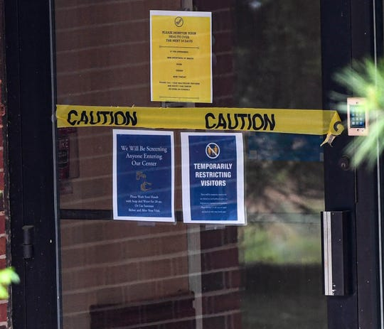 """A sign on a door at NHC HealthCare Anderson """"temporarily restricting visitors"""" and """"please monitor your health over the next 14 days"""" in April 2020."""
