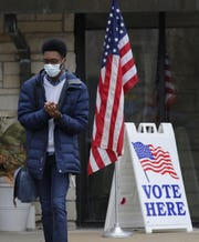 Lawrence University student Malcom Davis sanitizes his hands after voting Tuesday at Memorial Presbyterian Church in Appleton.