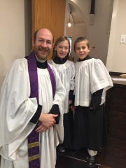 The Rev. John Lock, rector of Trinity Episcopal Church in Red Bank, with two of his three children, who serve as acolytes.