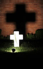 An illuminated small cross casts a larger shadow on the wall of a home on Woodridge Drive in south Abilene.