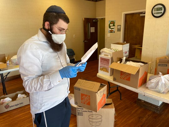 Rabbi Motty Rosenfeld sorts through several packages for Passover deliveries.