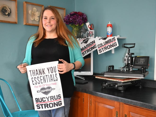 Rachel Striker, the owner of Bucyrus-based Print Happy, shows off one of her garden flags thanking essential workers.