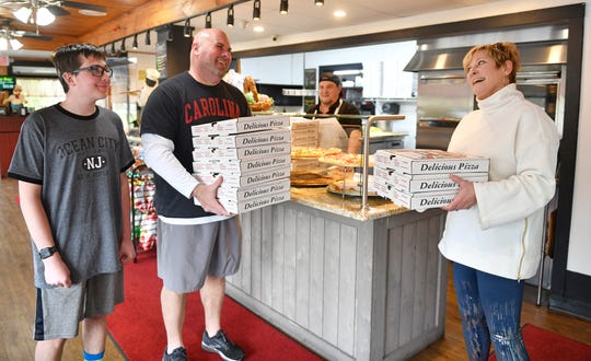 Teacher Ronn Flaim and his son Ronald, left, and Dina Deveney, who has a son that is part of Delsea Regional High School's SAVE program, pick up pizza kits donated by Danny's Pizza Pizzazz in Franklinville. Kits are delivered to students with special needs for a virtual lifeskills  slesson.