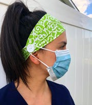 Sheila Newman, a nurse in Toms River, models a modified Ry-Bandz headband. The creator Ryann Jones started sewing buttons on the sides of the bands to protect healthcare workers' ears from being rubbed raw by medical masks as they care for COVID-19 coronavirus patients.
