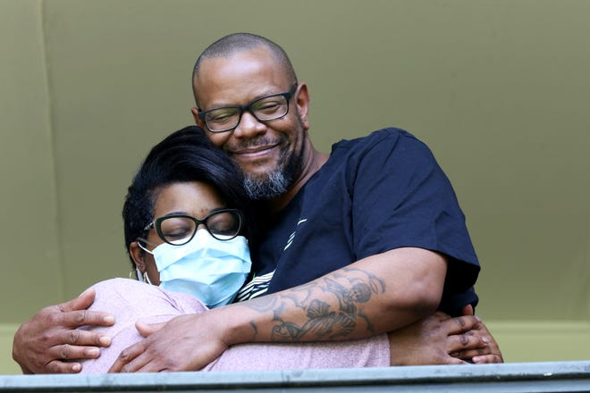 Jonathan Curtis, 40, hugs his longtime girlfriend, Allison Brown, 37, from the balcony of their Hartwell home, Tuesday, April 7, 2020. Both were diagnosed with COVID-19. Brown, who has lupus, was hospitalized for 12 days and was released April 5 and put under home quarantine. Curtis only experienced mild symptoms.
