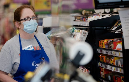 A Kroger employee wears a mask at Kroger on Tuesday, April 7, 2020, in Newport, Kentucky. Cleaning carts is one of the things Kroger is doing to limit the spread of the new coronavirus.