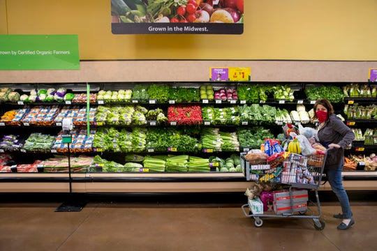 A shopper wears a mask while going through the produce section at Kroger on Tuesday, April 7, 2020, in Newport, Ky.
