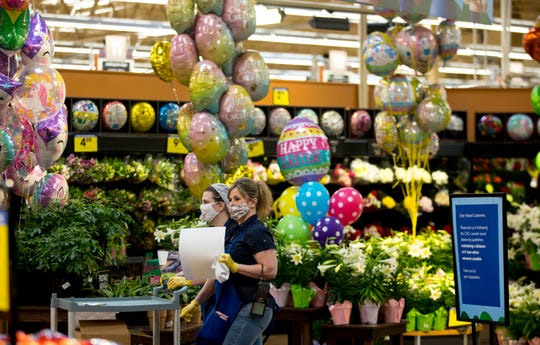 Kroger employees wear masks and gloves while walking past the floral section at Kroger on Tuesday, April 7, 2020, in Newport, Ky.  (Photo: Albert Cesare / The Enquirer)
