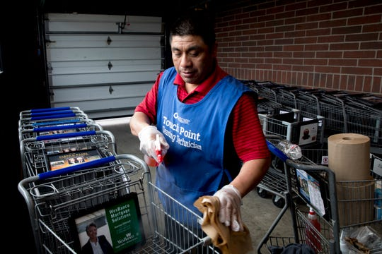 Desiderio Reynoso Morales disinfects shopping carts before they are used by patrons at Kroger on Tuesday, April 7, 2020, in Newport, Ky. Cleaning carts is one of the thing Kroger is doing to limit the spread of the new coronavirus.
