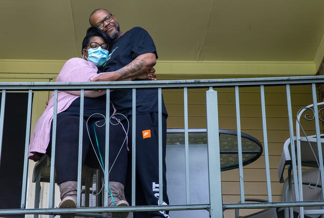 Jonathan Curtis, 40, hugs his longtime girlfriend Allison Brown, 37, from the balcony of their Hartwell home Tuesday, April 7, 2020, both were diagnosed with COVID-19. Brown who has lupus was hospitalized for 12 days and was released April 5 and under home quarantine. Curtis only experienced mild symptoms.