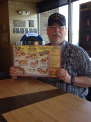 Bill Rubel displays a Waffle House menu in an undated photo. On Friday, April 3, 2020, Rubel became the first reported Montgomery County death due to the coronavirus.