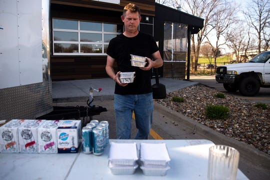 Michael Roberts, volunteering his time, sets out free take-and-bake boxes of pasta for anyone who needs them, on Tuesday, April 7, 2020, outside of Grumpy Goat Tavern in West Des Moines.