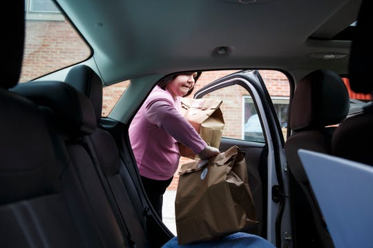 Chanie Jacobson loads Seder meals into a car to be delivered at Maccabee's Deli on Tuesday, April 7, 2020, in Des Moines. The Seder meal marks the beginning of Passover and is usually celebrated in large groups but with gatherings limited during the Coronavirus pandemic Maccabee's is delivering Seder meals to people at their homes.