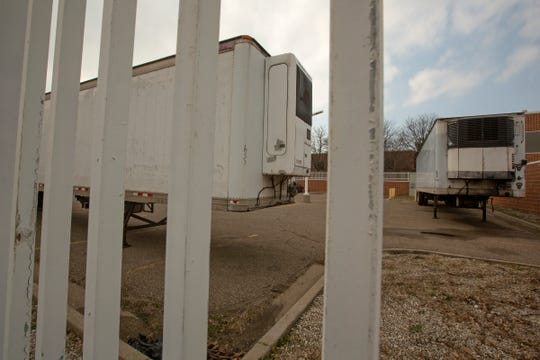 Two refrigerated trucks sit in a gated parking lot at the Wayne County Medical Examiner's Office in Detroit, Michigan on Tuesday, April 7, 2020. They are expected to be used for deaths from COVID-19.