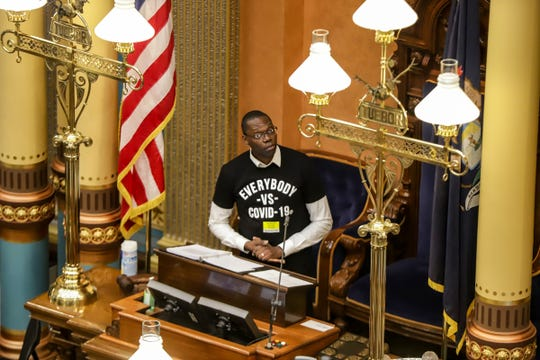 "Lieutenant Governor Garlin Gilchrist II wears a t-shirt that says ""Everybody vs. COVID-19"" as he leads the senate session to vote to extend the Michigan declaration of emergency until April 30th, at the Michigan State Capitol in Lansing, Mich. on Tuesday, April 7, 2020."