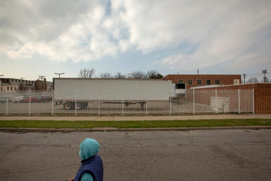A woman walks behind the Wayne County Medical Examiner's Office in Detroit, Michigan, where two refrigerated trucks are being stored for expected deaths from COVID-19. Photo taken on Tuesday, April 7, 2020.