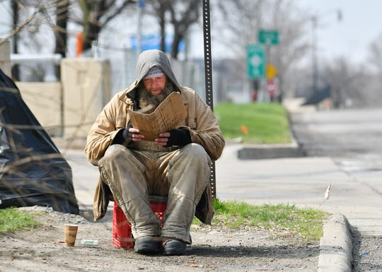 """Jay, who is 38 and did not want to give his last name, reads a Tom Clancy book while holding a sign that reads """"Homeless and Hungry, Anything Helps. Thank You and God Bless."""" Jay has been homeless on and off for 10 years."""