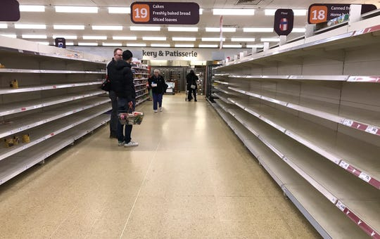 People stand in an aisle of empty shelves in a supermarket in London,  amid panic-buying due to the coronavirus outbreak on March 19.