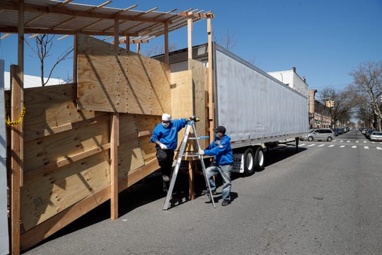Workers construct a barrier to obstruct the street level view of a loading platform leading into refrigerated trailers serving as a makeshift morgue at Wyckoff Heights Medical Center, Monday, April 6, 2020, in the Brooklyn borough of New York.
