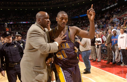 "Ron Artest is led off the court by Pacers special consultant Chuck Person after a brawl near the end of a 2004 game between the Pistons and the Pacers, later dubbed ""The Malice at the Palace."""