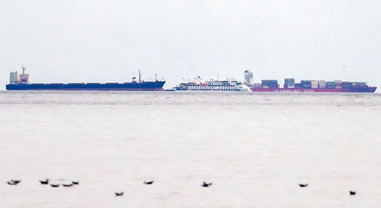 The Australian cruise ship Greg Mortimer, center, lies at anchor surrounded by two cargo ships off the port of Montevideo, Uruguay, Sunday, April 5, 2020. The Greg Mortimer with 211 people onboard has had at least 81 of them diagnosed with COVID-19 disease. (AP Photo/Matilde Campodonico)