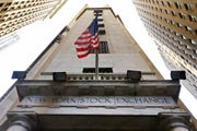 In this Friday, Nov. 13, 2015, file photo, the American flag flies above the Wall Street entrance to the New York Stock Exchange.