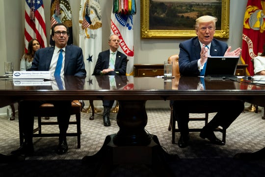 Treasury Secretary Steven Mnuchin listens as President Donald Trump speaks during a conference call with banks on efforts to help small businesses during the coronavirus pandemic, at the White House, Tuesday, April 7, 2020, in Washington. (AP Photo/Evan Vucci)