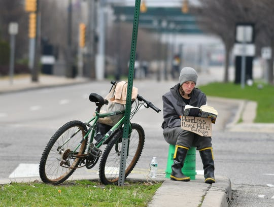"""Audrey, who is 32 and did not want to give her last name, holds a sign that reads """"Homeless Please Help. God Bless You!"""" while she reads a book of short stories near Bagley and Third Streets in Detroit on April 7, 2020."""