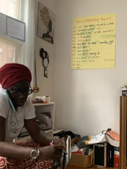 ABISA's Fatou-Seydi Sarr taking aid requests. The background shows a tracking system with family initials, how much money is being sent and what for.