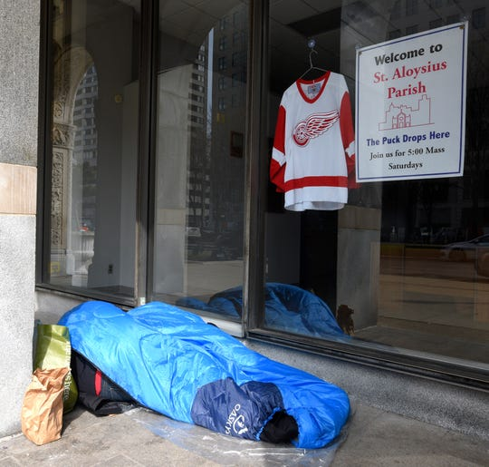 Two people sleep in one sleeping bag under the arches at St. Aloysius Catholic Church Parish and Neighborhood Services on Washington Blvd., Tuesday, April 7, 2020.