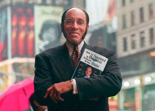 "This Aug. 17, 1997 file photo shows Earl G. Graves Sr. with his book ""How To Succeed In Business Without Being White"" in New York.  Graves Sr., who championed black businesses as the founder of the first African American-owned magazine focusing on black entrepreneurs, has died. He was 85. His son said Graves died Monday, April 6, 2020."