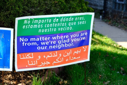 """A sign reading """"No matter where you are from, we're glad you're our neighbor,"""" outside of fundraiser Luz Viviana Meza's home in Detroit."""