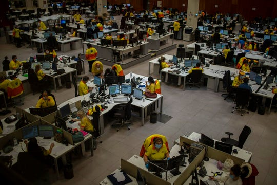 Health personnel work at the headquarters of the Emergency Medical System (SEM) in Barcelona that coordinates emergencies during the COVID-19 virus outbreak in Catalonia, Spain, Monday, April 6, 2020.