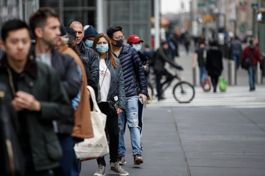 Customers wearing protective face masks to protect against the coronavirus, wait in line outside a Whole Foods supermarket on 6th Avenue, in New York on March 20.