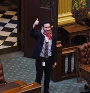 Rep. Abdullah Hammoud gives the thumb up as he checks in during attendance call as the Legislature holds a highly unusual session Tuesday to vote whether to extend Gov. Gretchen Whitmer's state of emergency at the State Capitol in Lansing, Tuesday, April,7, 2020.