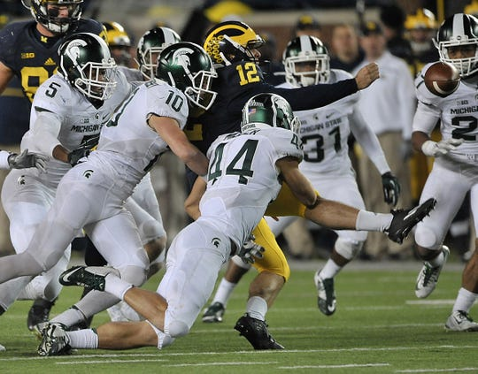 Michigan punter Blake O'Neill (12) loses the ball on the last play of the game, with Michigan State's Jalen Watts-Jackson picking up the ball and running it into the end zone for the victory in 2015.