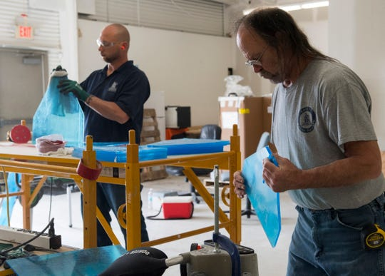 Garmong Construction employees Jerry Feldpausch, left, and Tom Hudson sand the edges of plexiglass as they fabricating mobile sneeze guards to help protect healthcare office workers during the COVID-19 pandemic in Evansville, Ind., Tuesday afternoon, April 7, 2020.