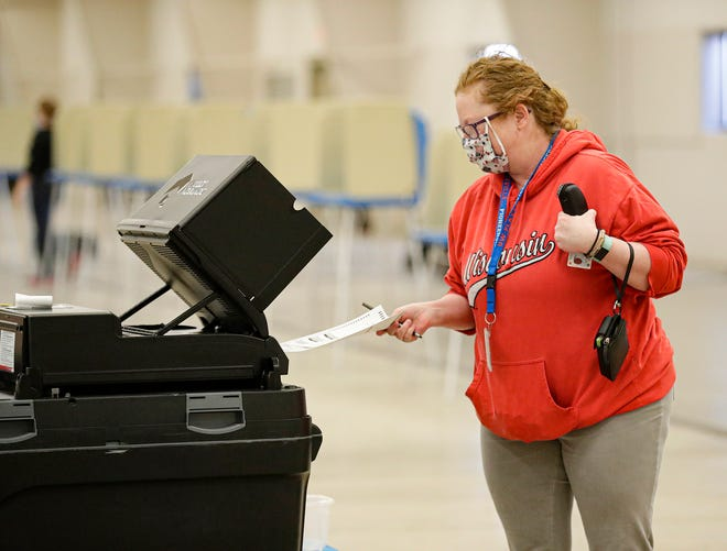 Christina Butzen, of Fond du Lac, feeds her Wisconsin primary ballot into the counting machine April 7, 2020, at the Fond du Lac County Fairgrounds polling location in Fond du Lac, Wis. Due to the coronavirus, many voters turned out wearing protective face masks.