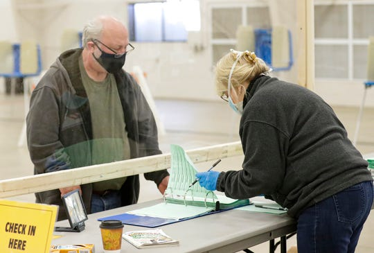 Ray Beilke, of Fond du Lac, picks up his Wisconsin primary ballot Tuesday at the Fond du Lac County Fairgrounds polling location in Fond du Lac. Due to the coronavirus, many voters turned out wearing protective face masks.