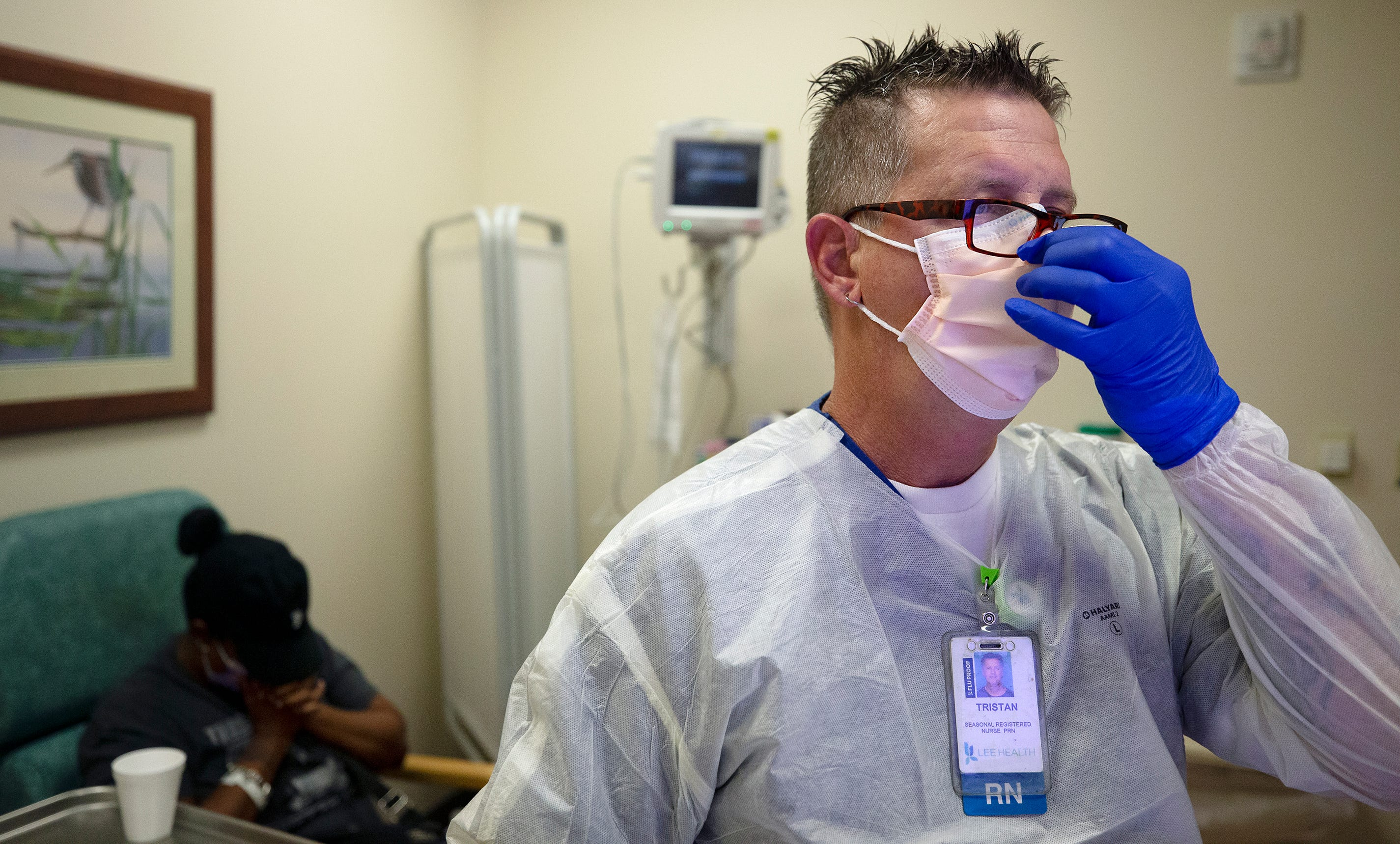 Emergency room nurse Tristan Manbevers checks in a woman complaining of COVID-19 symptoms at Gulf Coast Medical Center in Fort Myers, Fla.