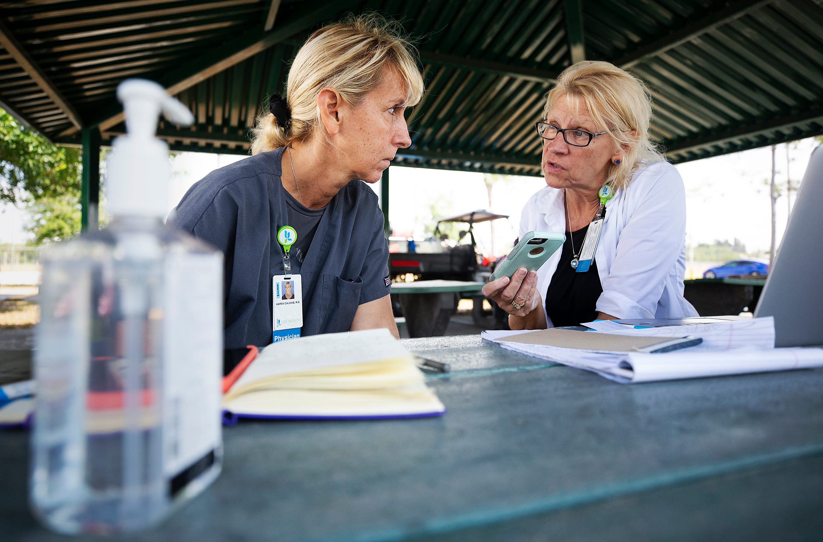 Dr. Karen Calkins and Kathy Richards-Bessshare give COVID-19 testing updates on a conference call at a mobile testing site setup in a park in Cape Coral, Fla.